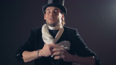 destruição : A male illusionist is showing a magic trick with untying of a scarf