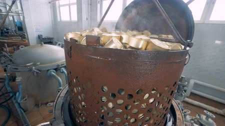 digesting : A pile of tin cans in a rusty container is being elevated from a boiler Stock Footage
