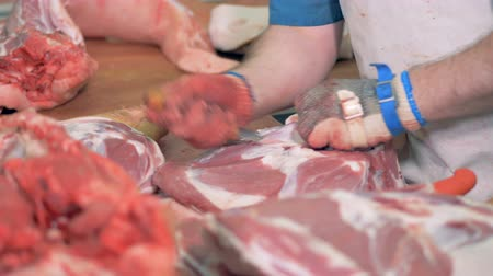 açougue : Small pieces are being cut out from a meat carcass by a butcher Vídeos