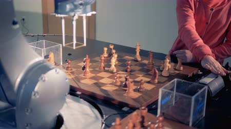 piskopos : A robotic arm and a little girl are rearranging chess pieces Stok Video