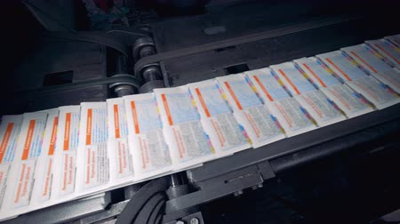 проходить : Fast movement of ready-made newspapers on the conveyor in a printing house.