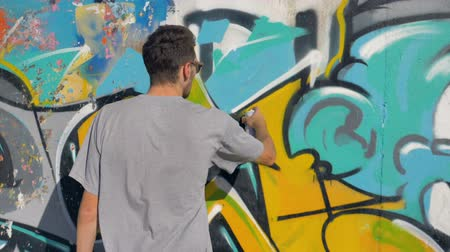 привлекать : Artist is painting a yellow letter on the wall, close up.