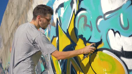 ghetto streets : Graffiti artist is painting a black triangle on the yellow letter, right view.