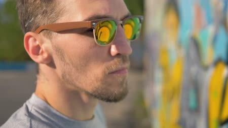привлекать : Graffiti artist portrait. Graffiti artist is painting, wall is reflecting in his sunglasses.