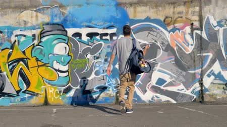 привлекать : Graffiti artist is coming up to the wall, shaking a spray paint and starting to draw. Стоковые видеозаписи