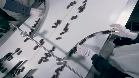 identical : Two factory workers are sorting chocolate candies which are then moving in different directions