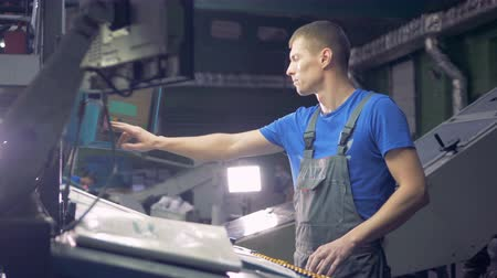 zařízení : Engineer works with industrial equipment using touchscreen.