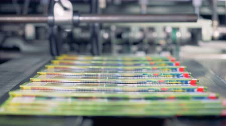 picked up : Portions of coloured journals are getting collected from a conveyor belt by a person