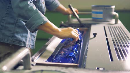 tray : A man is leveling blue paint in a tray of a printing machine