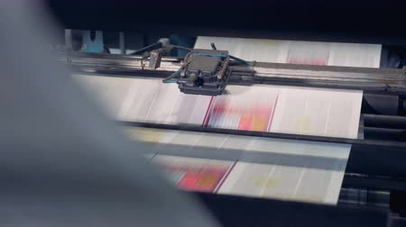 sheet : Uncut printed paper sheets are being processed by industrial equipment and moving along it in an upward direction