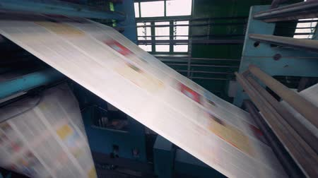 кампания : Fresh daily newspapers rolling on a printing equipment. 4K. Стоковые видеозаписи