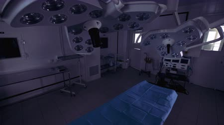 ér : A couple of surgical lamps hanging above the operation table is getting switched on