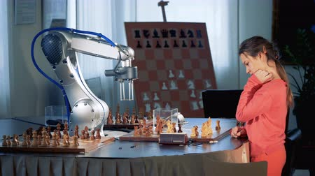çivit : Smart scgool girl playing chess with a robotic arm, chess robot. Child genius concept.