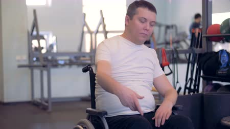 инвалидность : A disabled man is stretching his arms and shoulders while sitting in a wheelchair