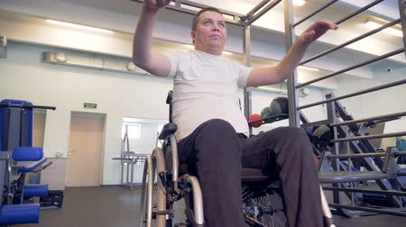 paralympics : Workout process of a male wheelchair invalid in a gym