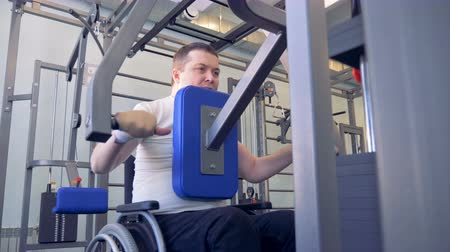 paralympic : A handicapped person in a wheelchair is doing exercises with a lift-weighting machine