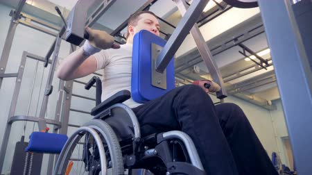 paralympics : Bottom view of an lift-weighting exercising process of a disabled man