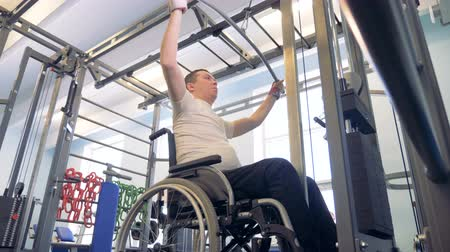 paralympics : Training process of a disabled man in a wheelchair with a weight-lifting mechanism