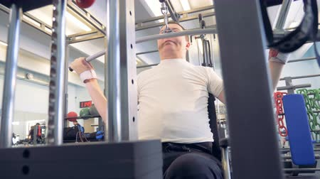 paralympic : Front view of a man in a wheelchair lifting weights with an exercise machine