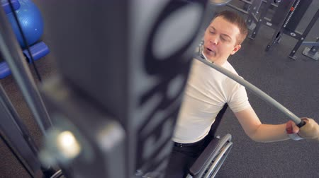 physically : Top view of an invalid in a wheelchair pulling a metal bar and lifting weight Stock Footage