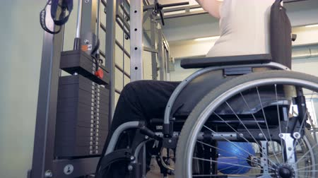 willpower : Side view of a disabled man lifting weights in a gym while sitting in a wheelchair