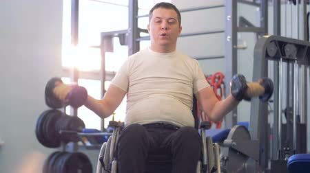 çabaları : Footage of a gym facility with a disabled man exercising in it Stok Video