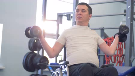paralympics : Training session of a disabled man with two dumb-bells in a gym