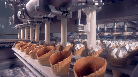padronizada : White narrow pipes are pumping ice-cream filling into waffle cones Vídeos