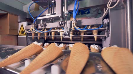 substância : Metal tongs are relocating ice-cream cones to an ongoing conveyor belt