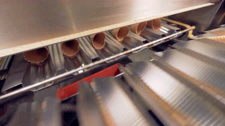 oplatka : Empty waffle cones are rapidly removed from a moving conveyor belt