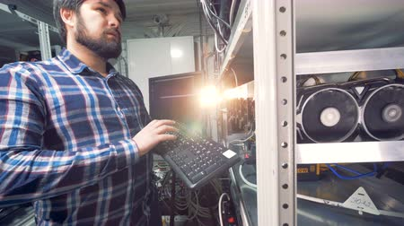 mining farm : Male IT Technician Working in cryptocurrence mining factory.