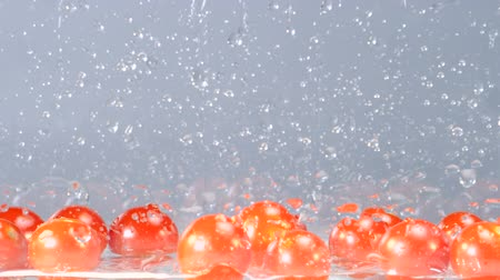into the camera : Orange tomatoes are rapidly falling into a tank with some water at the bottom