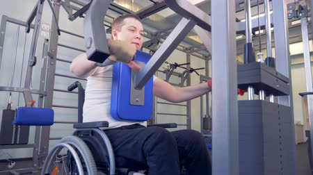 paralympics : Disabled man does strengths exercises for back on training apparatus.