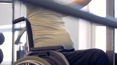willpower : Disabled athlete in a wheelchair getting ready for training in gym.