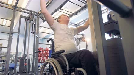 paralympics : Disabled man makes exercises in a gym at training apparatus. Stock Footage