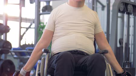 resistência : Handicapped man on wheelchair working out with dumbbell in a gym.