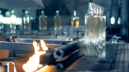 heat resistant : Automative press is slowly removing glass bottles from an annealing conveyor belt