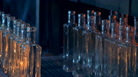 artigos de vidro : Bottles made of glass are reflecting fire light and are being moved by the press