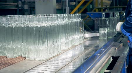 unfilled : Factory employee is putting glassy bottles onto the conveyor belt Stock Footage