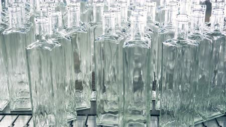 abriu : A pile of transparent newly-made bottles being pushed onto the conveyor belt