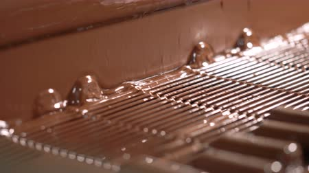 gênero alimentício : Candy bars are poured with liquid chocolate. Close-up.