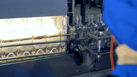 пивоваренный завод : Empty bottles go on a line, while a factory worker watches the technology. 4K.