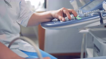 umbigo : Close up of doctors hands managing an ultrasound console and sensory device. Vídeos