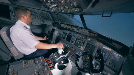 pilot in command : One pilot turns a plane to the left, sitting in a flight simulator. 4K.
