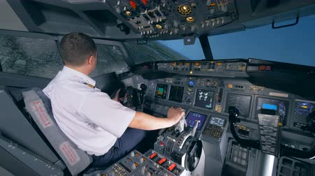 pilot in command : An airman sits in a flight simulator and turns a plane to the left. 4K.