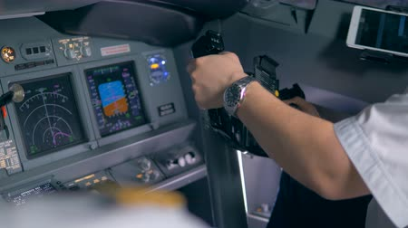aircrew : A pilot turns the steering wheel, close up.