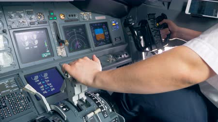 pilot in command : A pilot switches a lever and steers, close up.