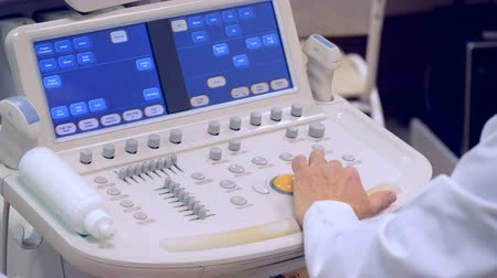 манипуляция : An ultrasound panel is being regulated by a doctors hand
