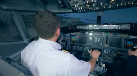 aircraft cabin : Two airmen in flight simulator, holding helms in a cockpit. 4K.