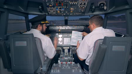 pilótafülke : Pilots read a manual in a cockpit of a flight simulator. 4K. Stock mozgókép